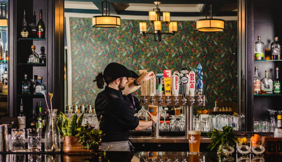 Bar tender pulls draft beer in downtown Cary