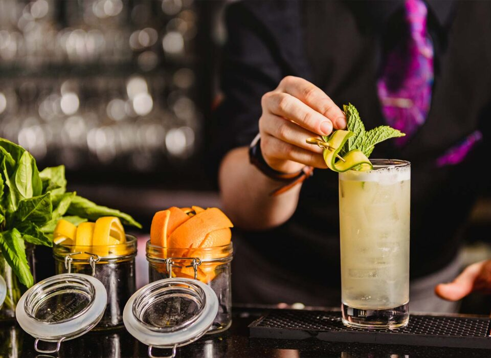 bartender adding mint and sliced cucumber to garnish a drink at the bar