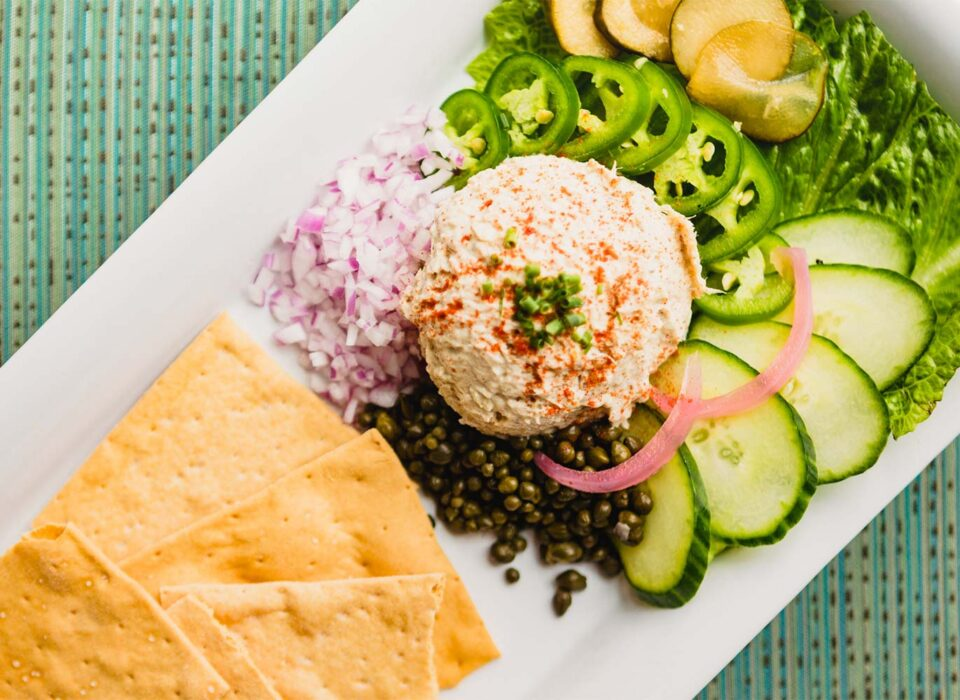 hummus and chip dish with onions, cucumbers, peppers, and capers surrounding it