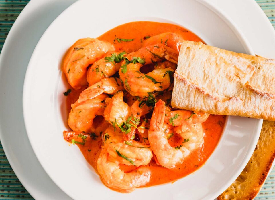 cooked shrimp dish with garlic bread on a white plate