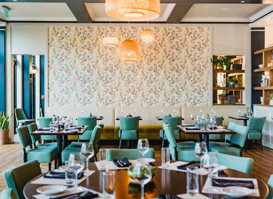 restaurant dining area with green cushioned chairs, banquet seating and floral wallpaper