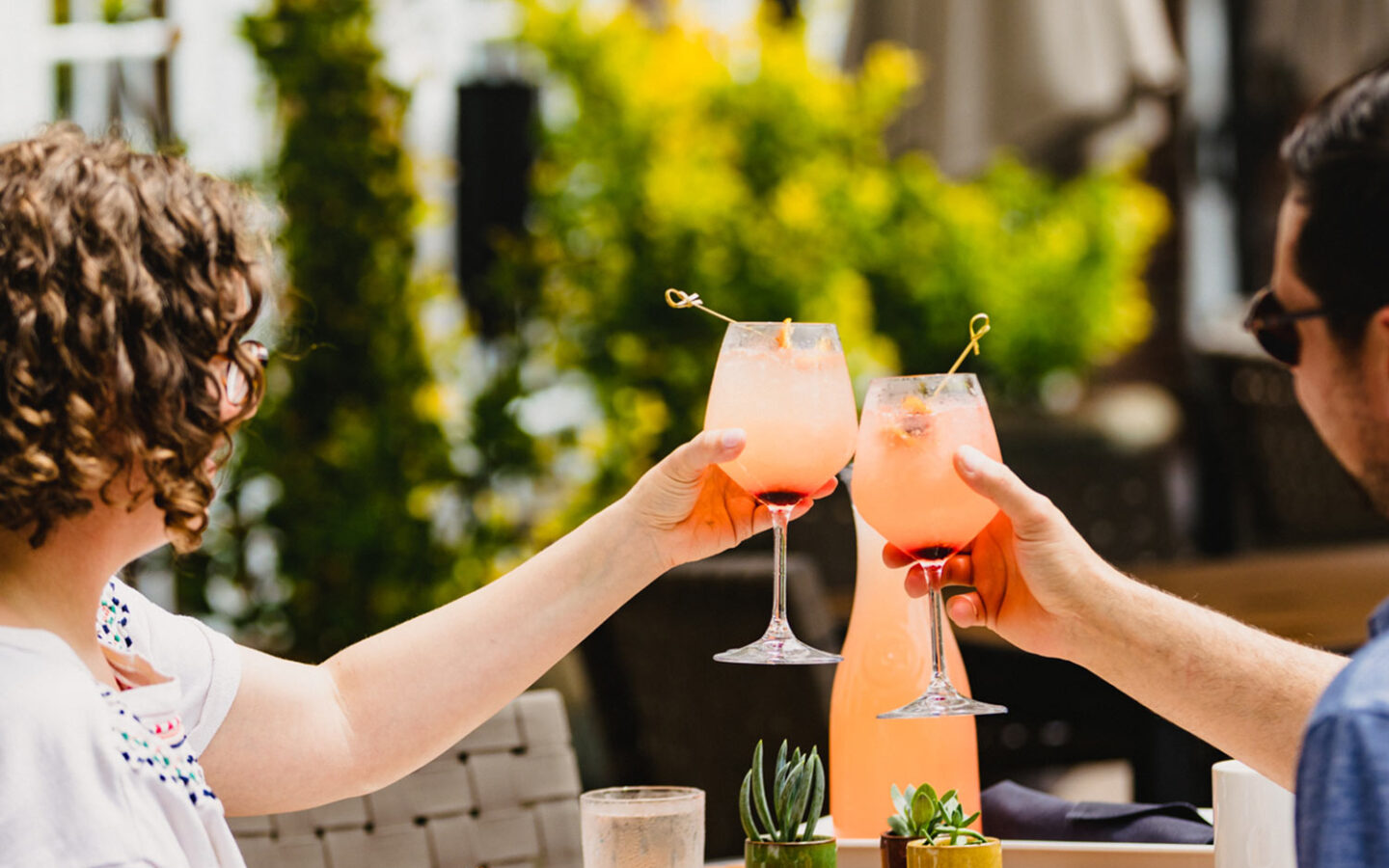 two people dining outdoors holding their cocktail glasses together