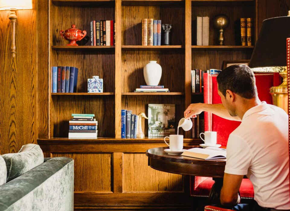 man sitting in a large red chair pouring milk into his coffee in front of a built-in bookcase