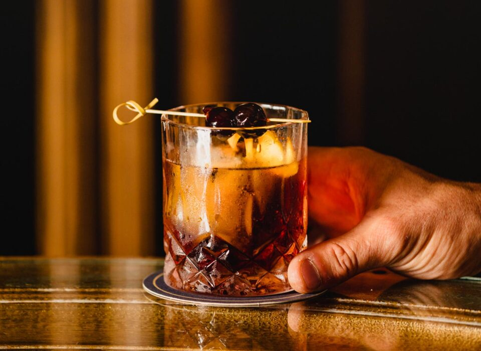 closeup of a hand holding a dark cocktail garnished with two berries