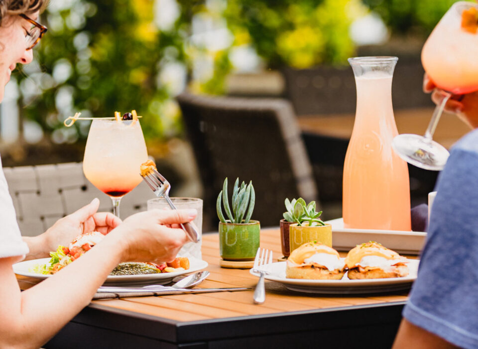 two people eating outdoors on a terrace during daytime